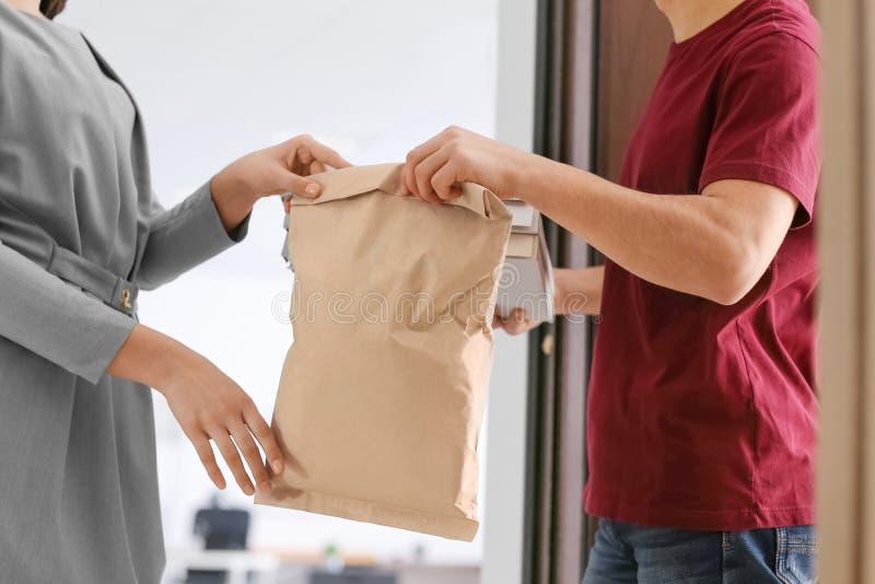 Заказ молодой женщины получая от курьера Обслуживание доставки еды стоковое изображение