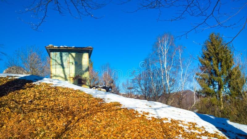 Закамуфлированная деревянная хата для охотиться в горах в зиме стоковое изображение rf