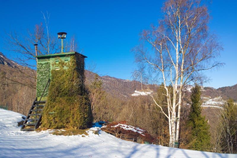 Закамуфлированная деревянная хата для охотиться в горах в зиме стоковая фотография