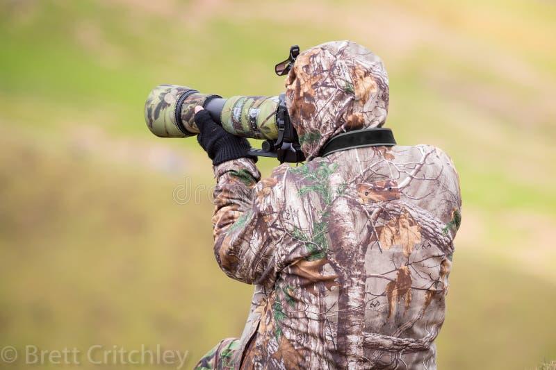 Закамуфлированный фотограф используя камеру стоковая фотография