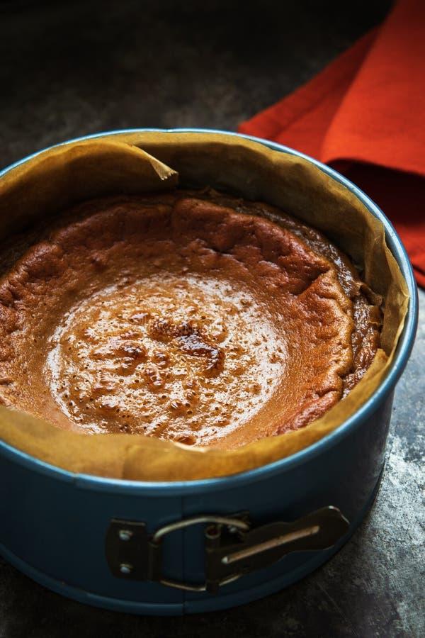 Заканчивать свежо испеченный чизкейк карамельки в прессформе торта на темной предпосылке стоковые изображения rf