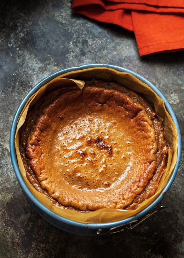 Заканчивать свежо испеченный чизкейк карамельки в прессформе торта на темной предпосылке стоковые изображения
