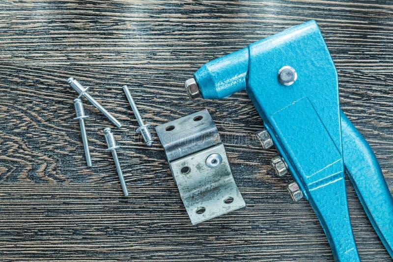 Заклепывать винты заклепок плоскогубцев на деревянной доске стоковая фотография