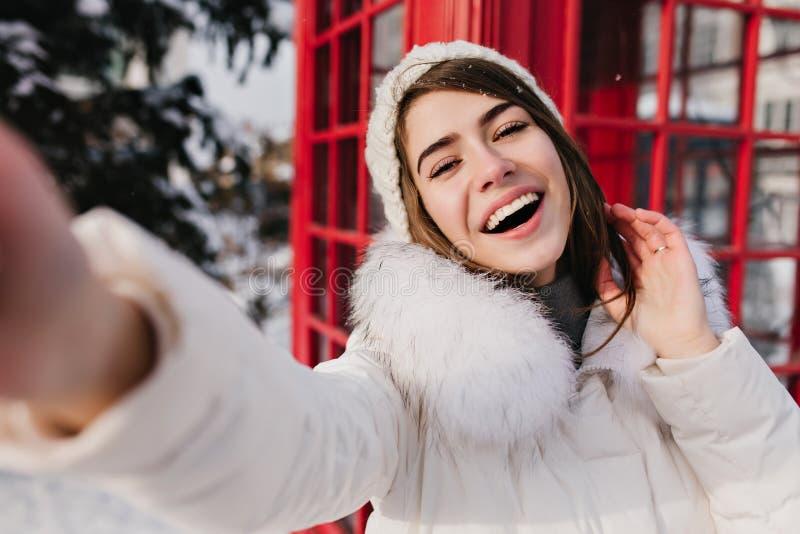 Заколдовывая девушка в белой шляпе делая selfie перед красной звонк-коробкой На открытом воздухе портрет смеяться кавказский прин стоковые изображения