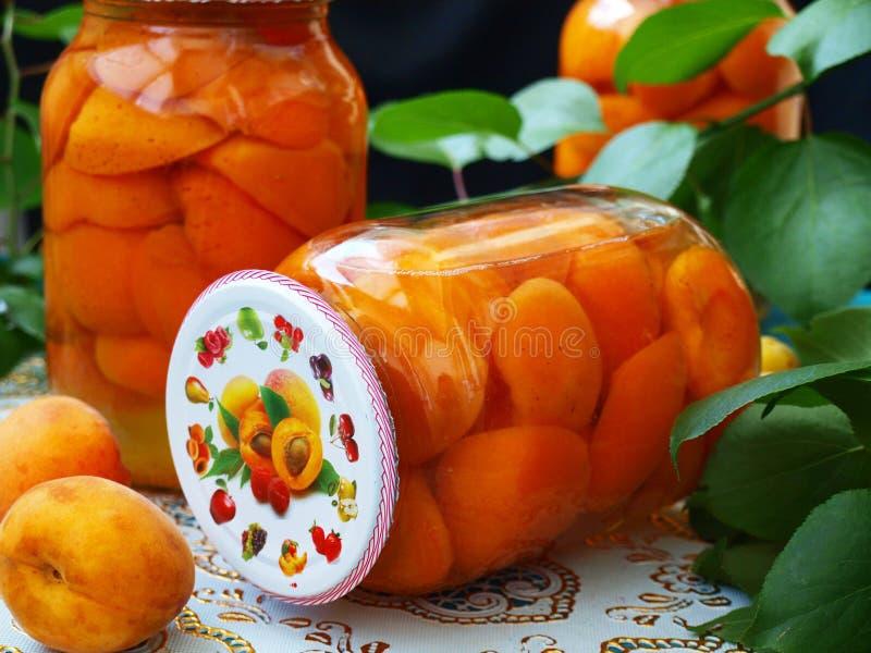 Законсервированные абрикосы в сладком сиропе в 2 опарниках на таблице стоковая фотография rf
