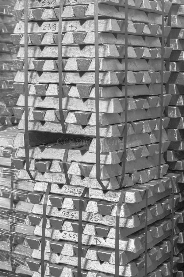 Закройте вверх алюминия на хранении слитка паллета в крытом складе для экспорта как промышленная предпосылка Алюминиевый миллиард стоковое фото
