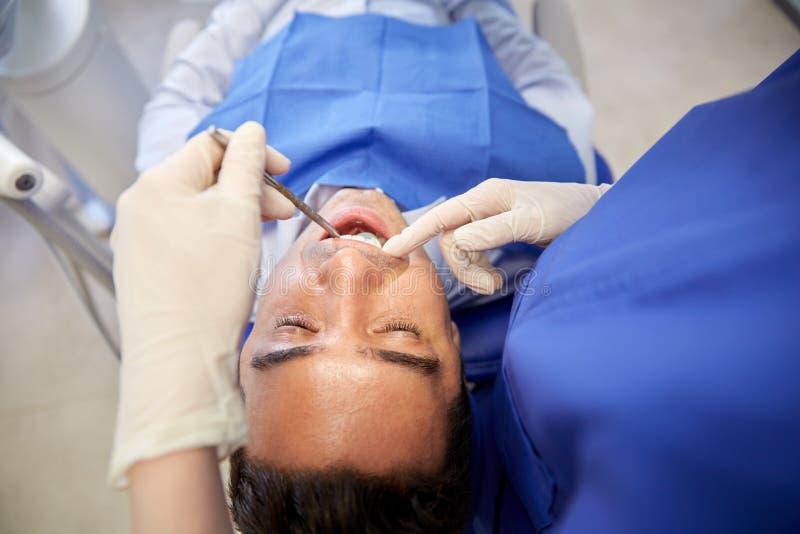 Закройте вверх дантиста проверяя мужские терпеливые зубы стоковые фото