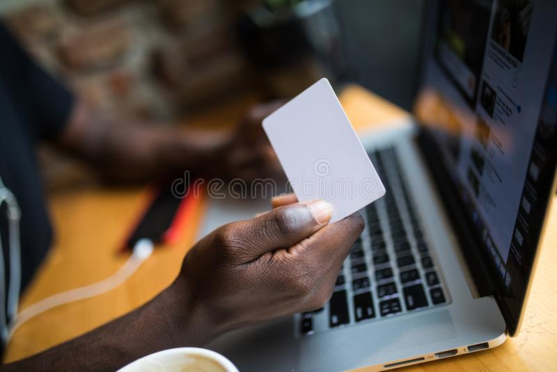 Закройте вверх афро американских рук человека с белой пустой карточкой для космоса экземпляра adv перед предпосылкой компьтер-кни стоковое изображение