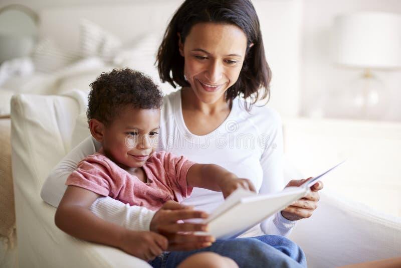 Закройте вверх Афро-американской молодой взрослой матери сидя в кресле читая книгу с ее годовалым сыном 3 на ее колене, cl стоковые фото