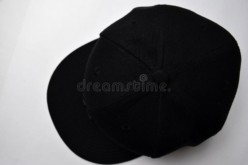Закройте вверх бейсбол щелкните назад черноту цвета крышки изолированную на белой предпосылке стоковая фотография