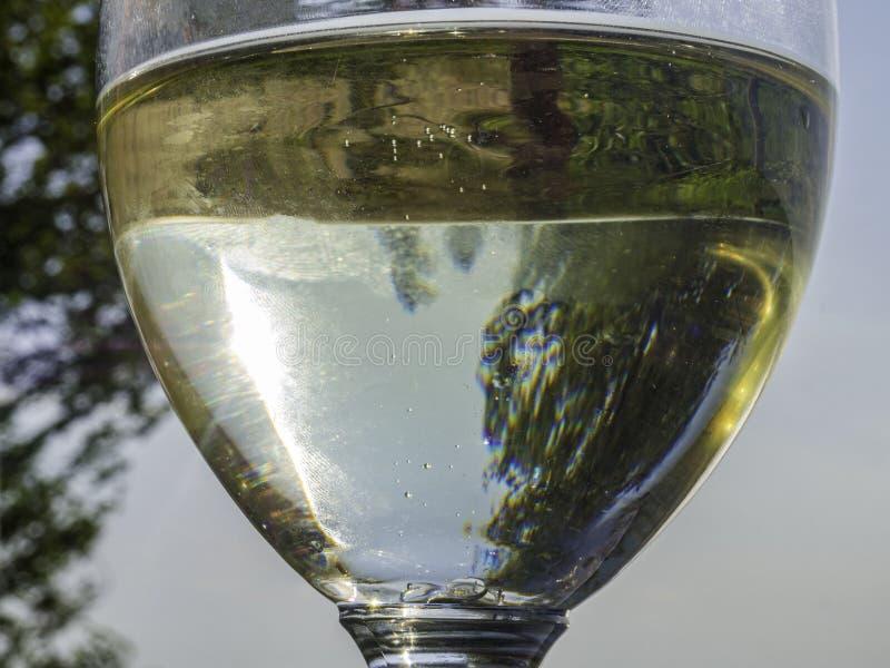 Закройте вверх белого вина, стекла сидра с красивым тонизированным видом на море, стоковые изображения rf