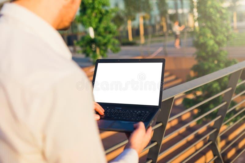 Закройте вверх бизнесмена использующ ноутбук пустого экрана outdoors стоковые изображения