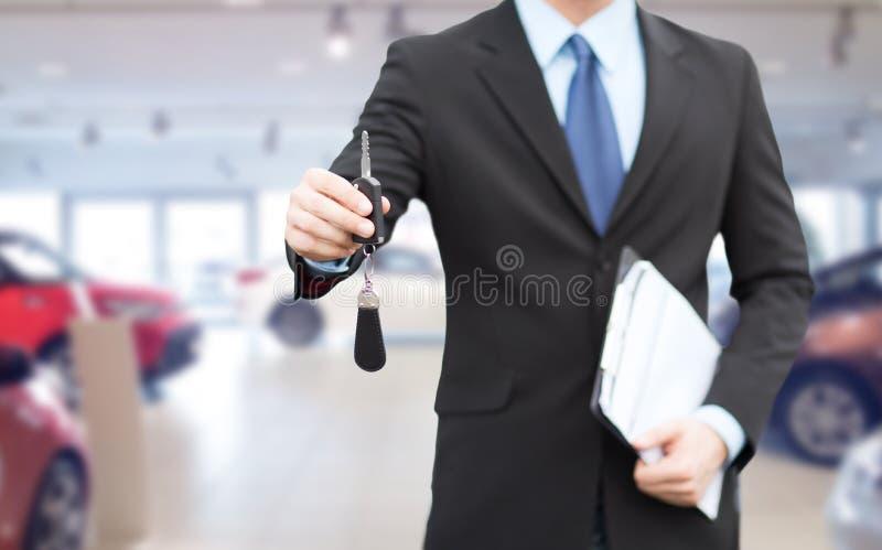 Закройте вверх бизнесмена или продавца давая ключ автомобиля стоковое фото rf