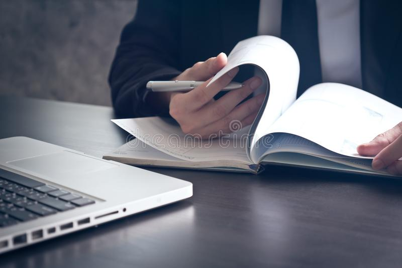 Закройте вверх бизнесмена проверяя документы на столе офиса стоковая фотография rf