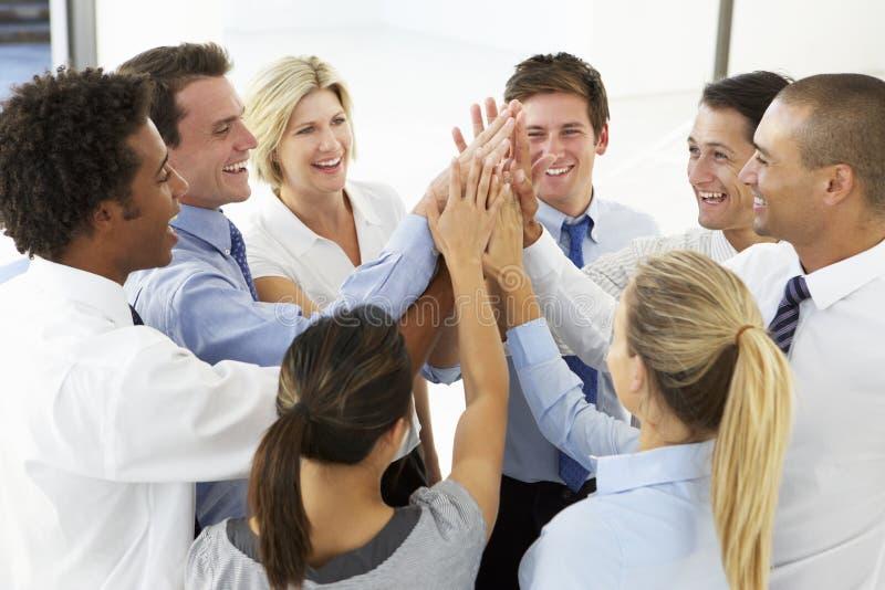 Закройте вверх бизнесменов соединяя руки в тренировке тимбилдинга стоковое фото