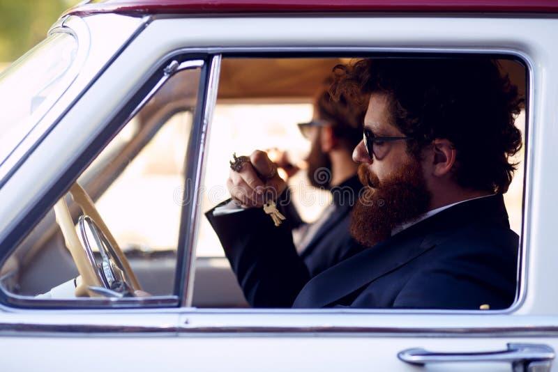 Закройте вверх 2 бородатых людей, в солнечных очках и черных элегантных костюмах, куря сигареты внутрь винтажного автомобиля стоковое изображение rf