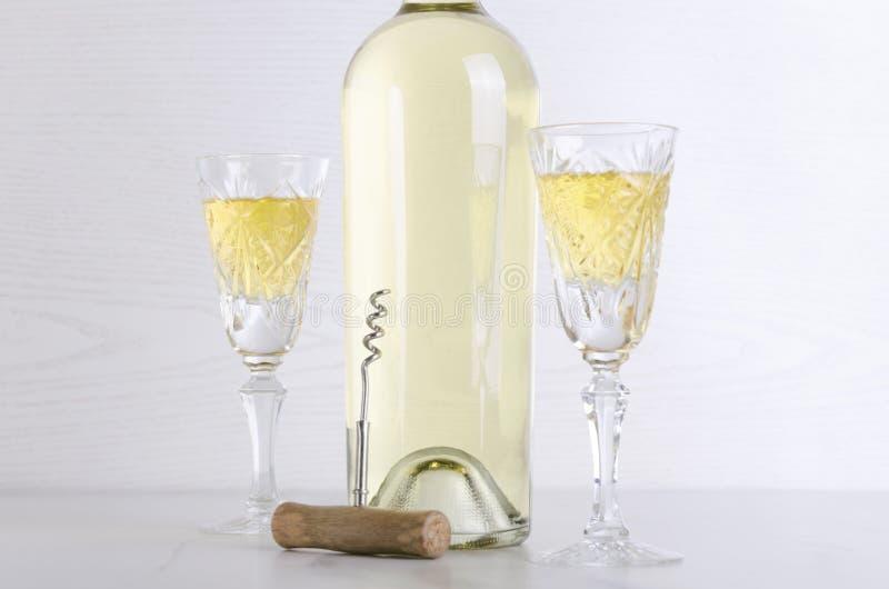 Закройте вверх бутылки белого вина и старых-fashiones стекел на белой таблице против яркой предпосылки стоковое фото rf