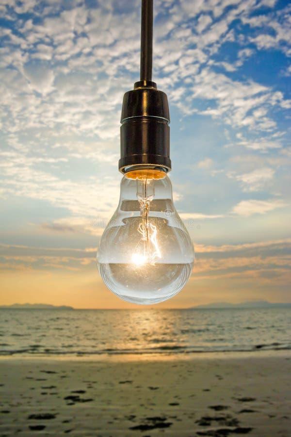 Закройте вверх винтажной электрической лампочки на предпосылке пляжа захода солнца стоковые изображения