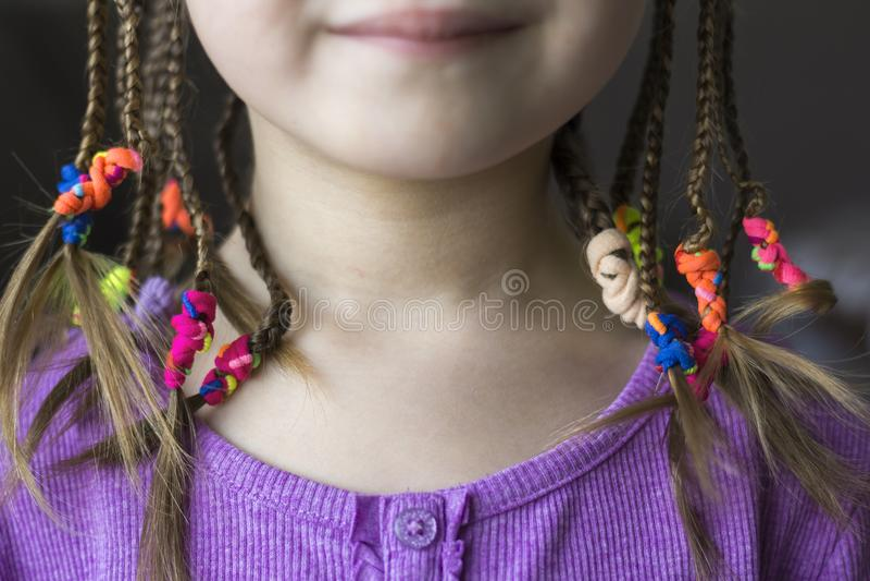 Закройте вверх волос оплетки маленькой девочки с красочными круглыми резинками стоковые фото