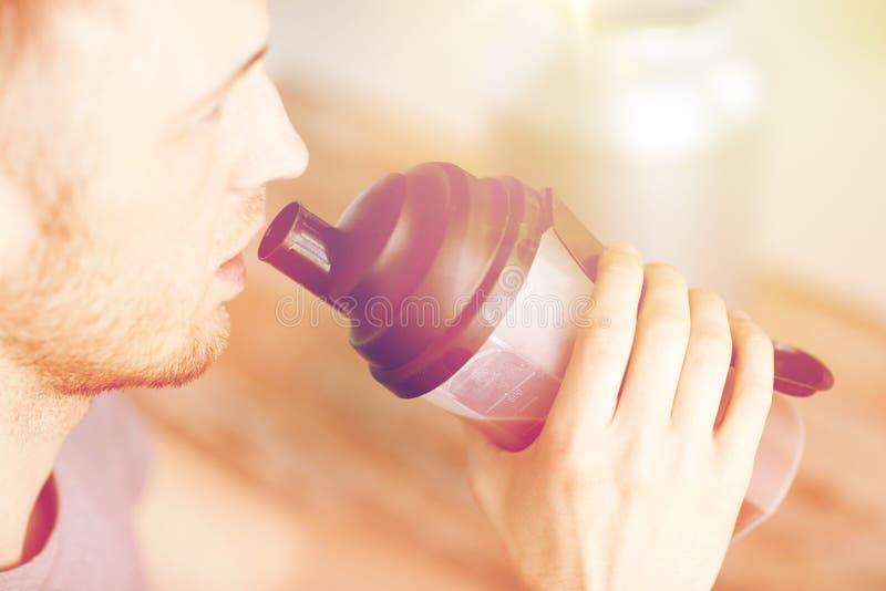 Закройте вверх встряхивания протеина человека выпивая стоковые изображения rf