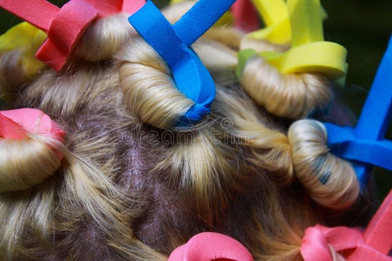 Закройте вверх головы европейской женщины со светлыми волосами и красочными старомодными curlers пены стоковая фотография rf