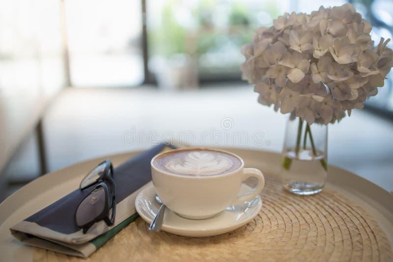 Закройте вверх горячего latte чашки кофе с искусством формы сердца молока с газетой и стеклами чтения на круглом столе стоковые фото