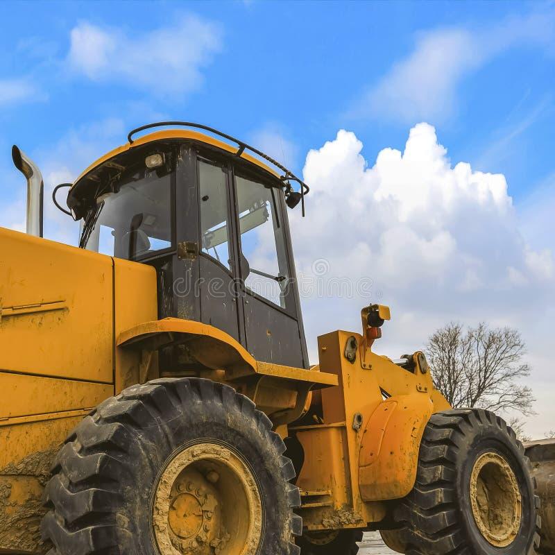 Закройте вверх грязного желтого затяжелителя с черными резиновыми колесами и пустой кабиной стоковые изображения rf