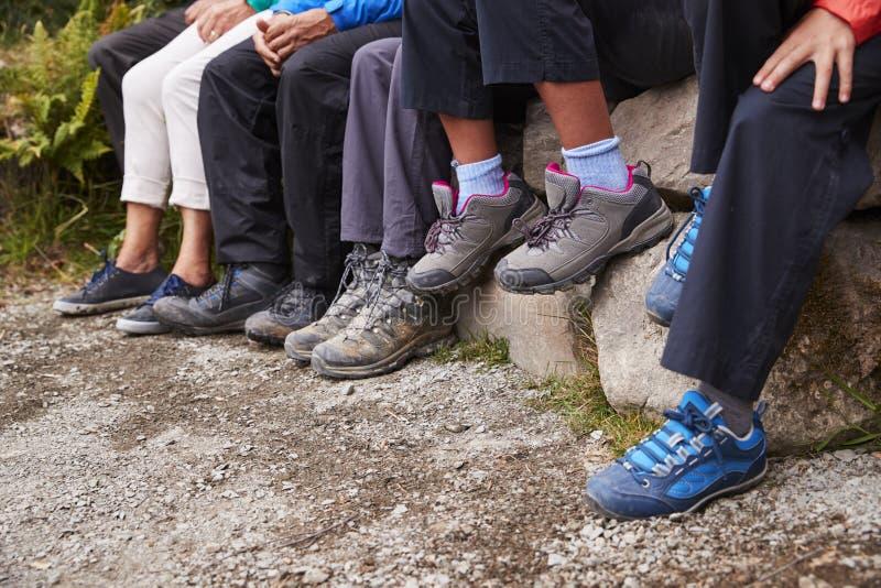 Закройте вверх грязных ботинок и брюк семьи сидя на камнях озером, деталью стоковые изображения rf