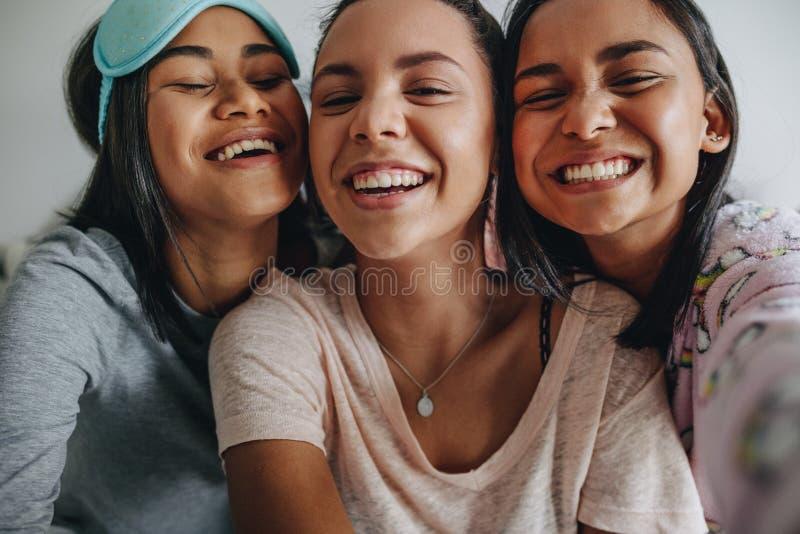 Закройте вверх 3 девушек принимая selfie стоковое изображение rf