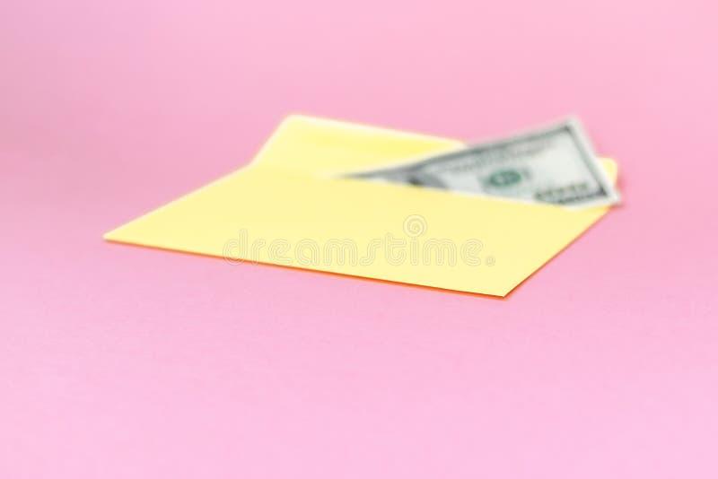 Закройте вверх денег в желтом конверте лежите на пастельной розовой предпосылке Клеймя насмешка вверх; вид спереди стоковые фотографии rf