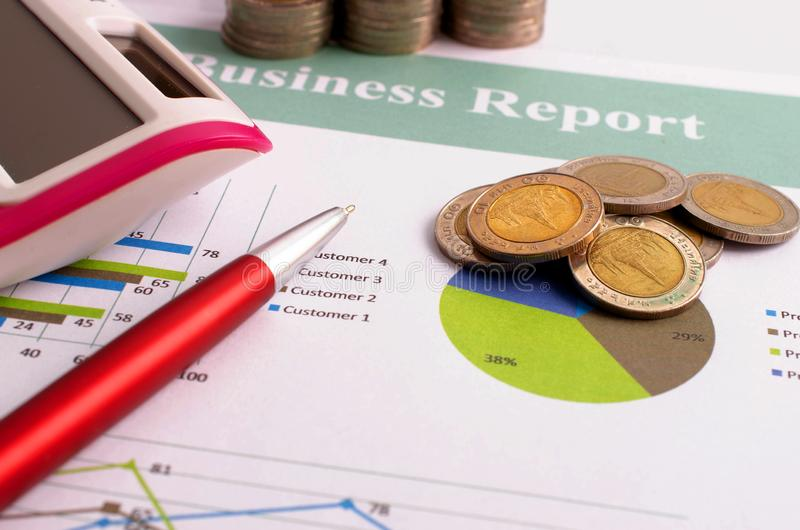 Закройте вверх денег монеток с красной ручкой и калькулятора на отчете о делового документа стоковая фотография