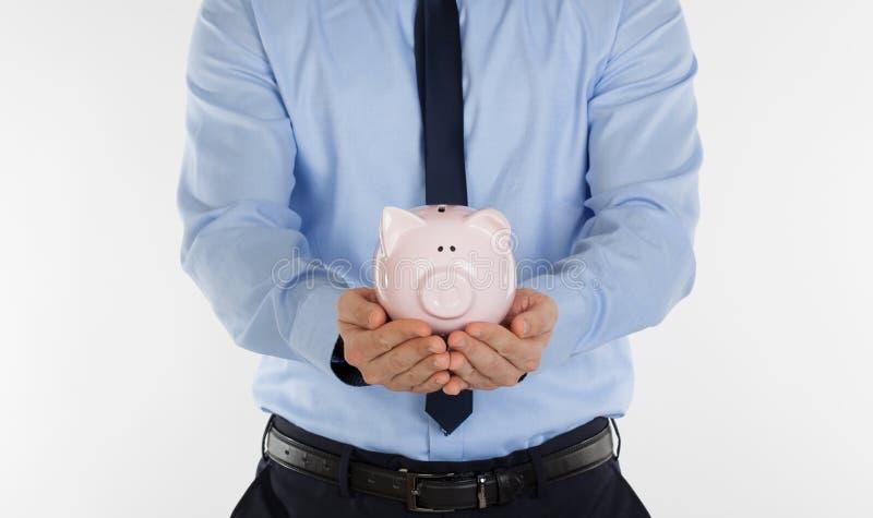 Закройте вверх денежного ящика свиньи удерживания бизнесмена стоковое изображение rf
