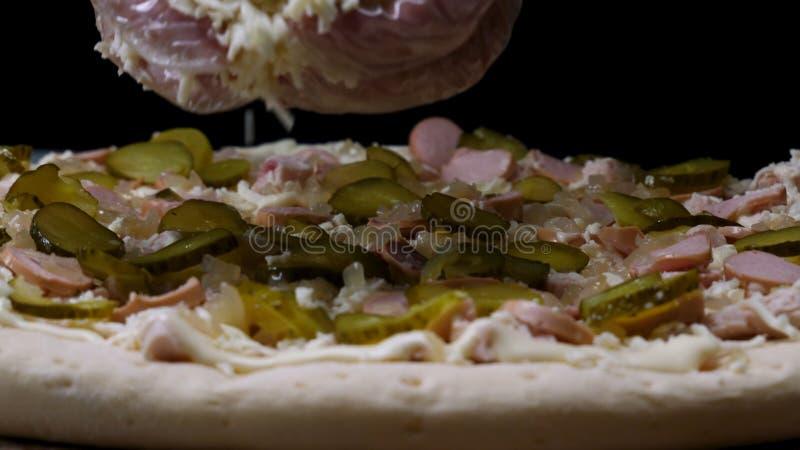 Закройте вверх для к рук в варить перчатки взбрызните пиццу с заскрежетанным сыром, концепцией итальянской кухни r Установка шеф- стоковые изображения