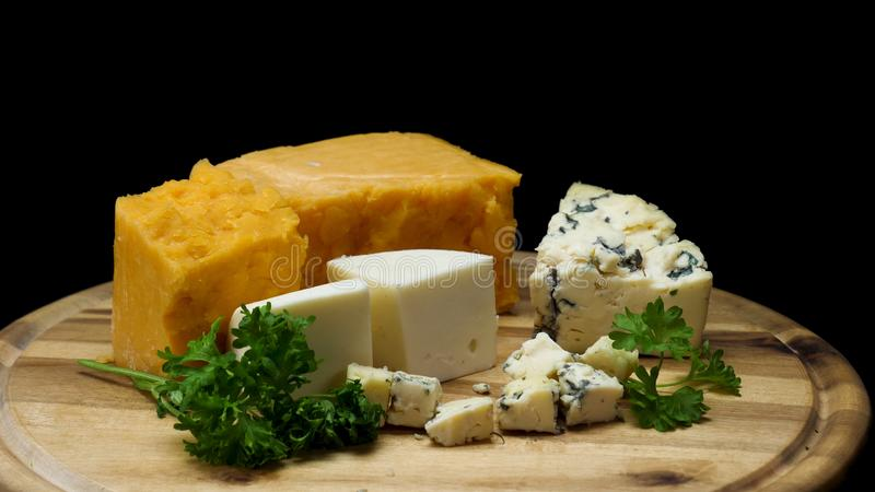 Закройте вверх для французских очень вкусных достигших возраста сыров choped и послужило на деревянной доске изолированной на чер стоковая фотография rf