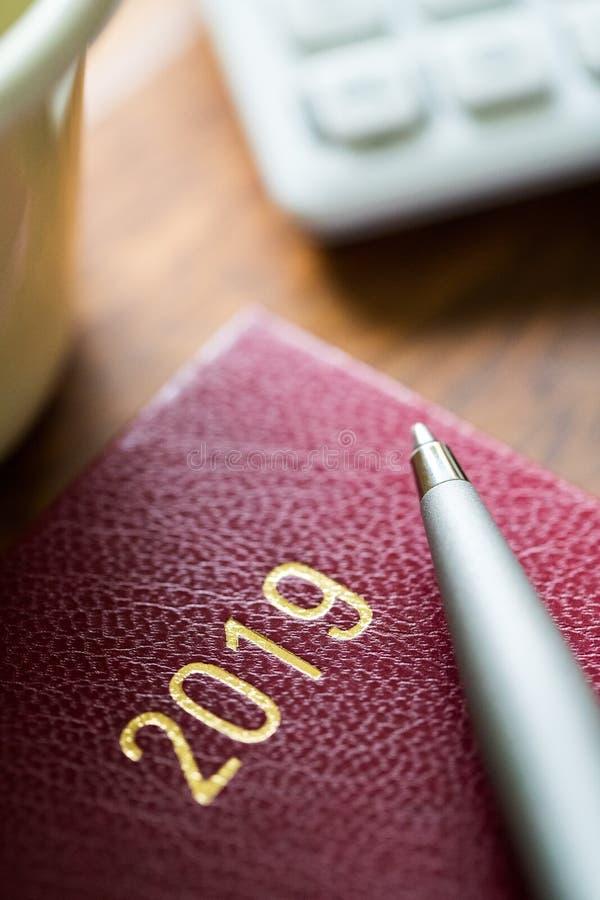 Закройте вверх дневника 2019 с ручкой и калькулятора на деревянном столе стоковое фото
