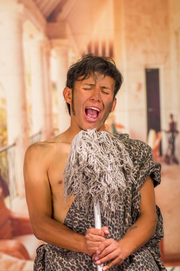 Закройте вверх доисторического человека делая смешные стороны к камере, поя и держа в его руках запачканный mop, в стоковое фото rf