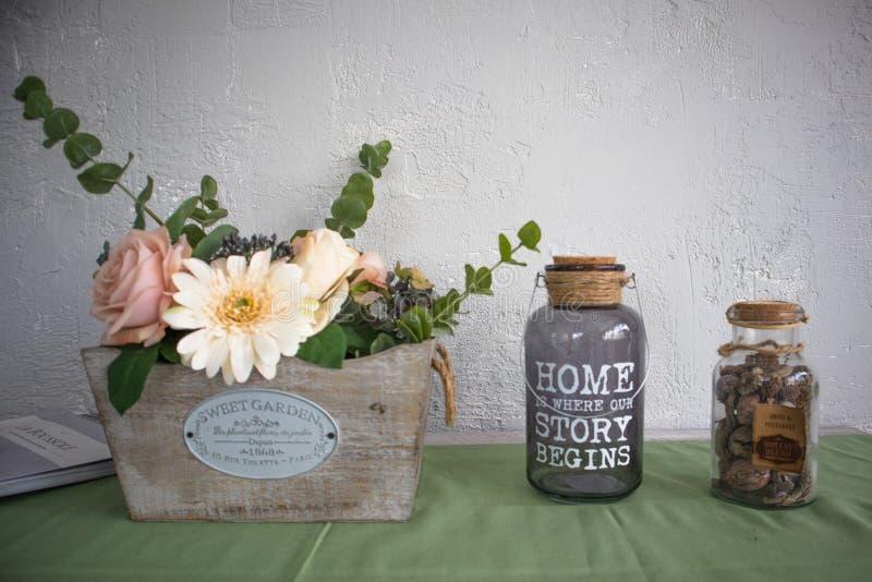 Закройте вверх домашних объектов внутреннего художественного оформления, цветков и 2 стеклянных бутылок на кухонном шкафе стоковые фотографии rf