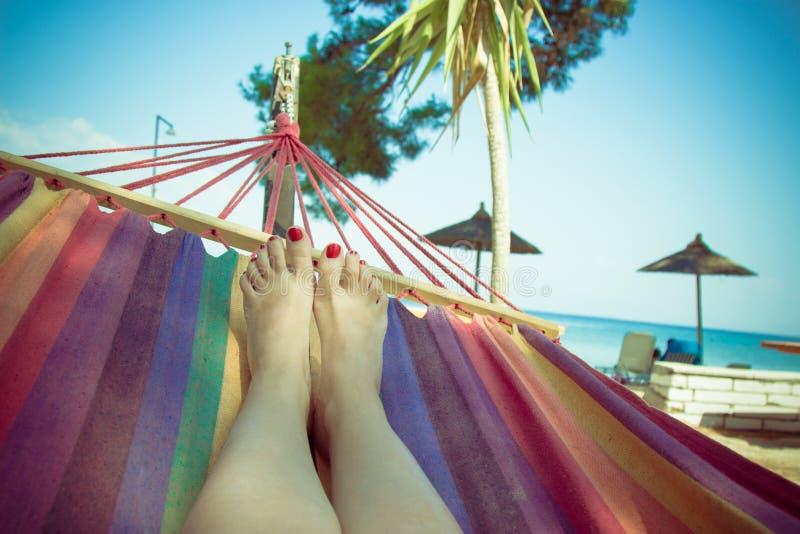 Закройте вверх женских ног на гамаке Пляж на заднем плане сумма стоковые фотографии rf