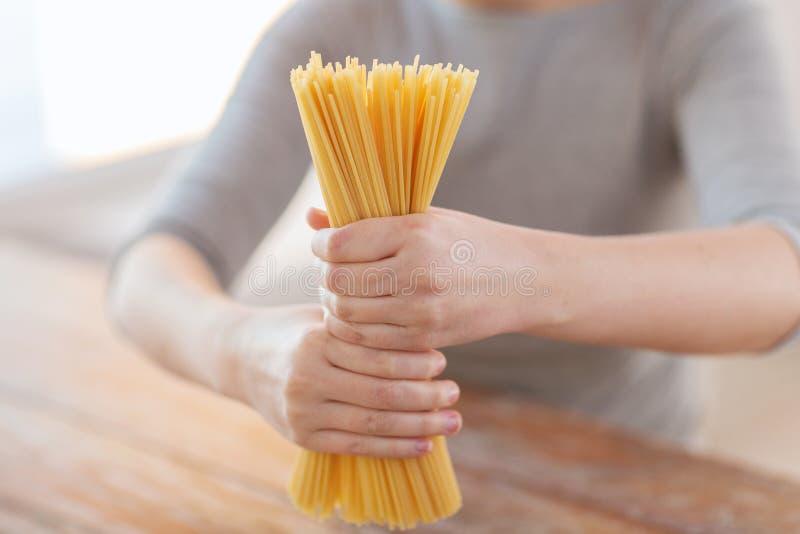 Закройте вверх женских рук держа макаронные изделия спагетти стоковые изображения rf