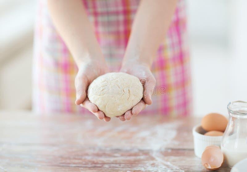 Закройте вверх женских рук держа тесто хлеба стоковая фотография