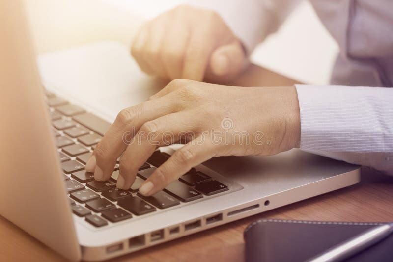 Закройте вверх женских рук печатая на клавиатуре компьтер-книжки стоковое изображение