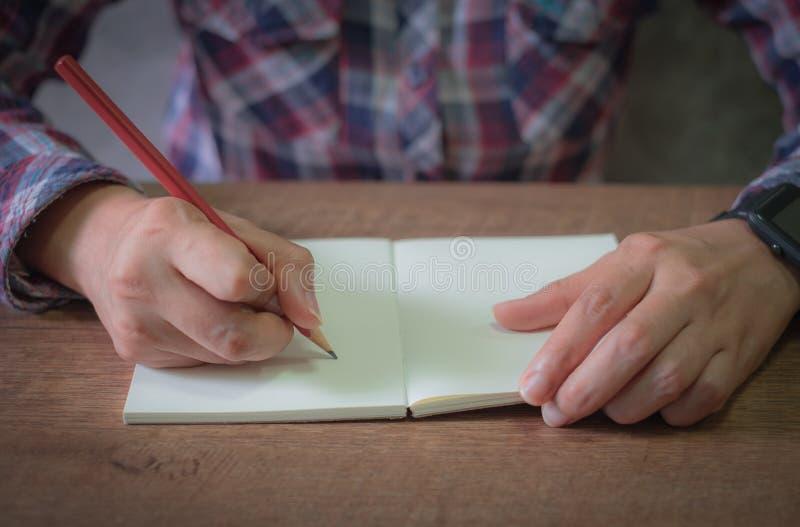 Закройте вверх женских рук писать в буклете пустом с красным карандашем стоковые фото