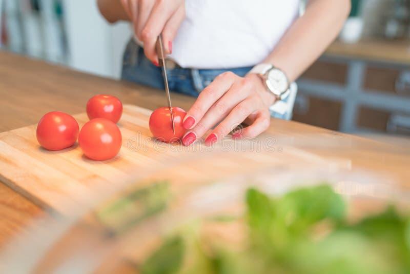 Закройте вверх женских томатов вишни ручной резки E салат овоща E o варить дома стоковые фотографии rf