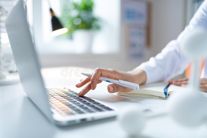 Закройте вверх женского химика держа белую ручку используя ноутбук стоковое фото rf