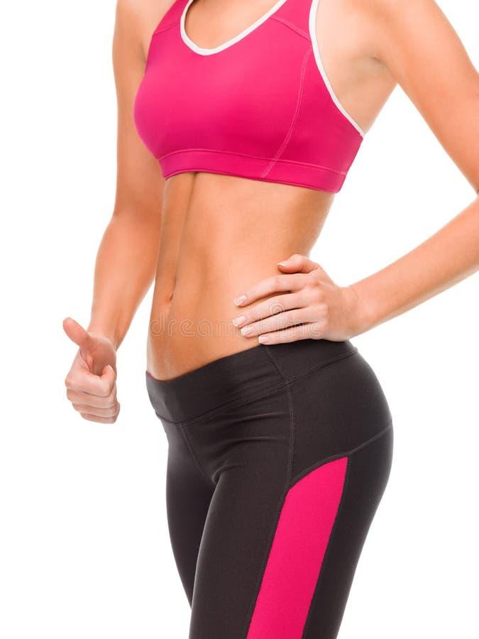 Закройте вверх женского abs и руки показывая большие пальцы руки вверх стоковое изображение