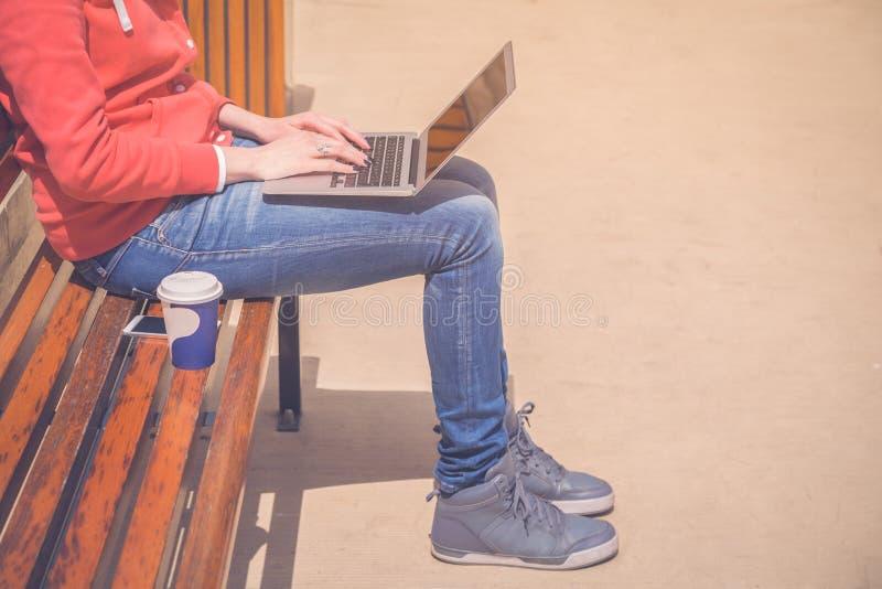 Закройте вверх женской работы на компьтер-книжке и сидя стенде n внешних стоковое фото rf