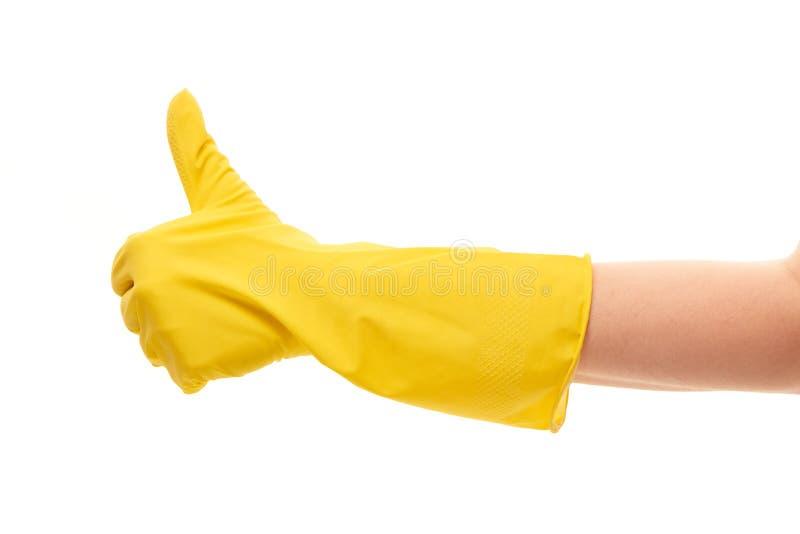 Закройте вверх женской руки в желтой защитной резиновой перчатке показывая большие пальцы руки вверх по знаку стоковое изображение