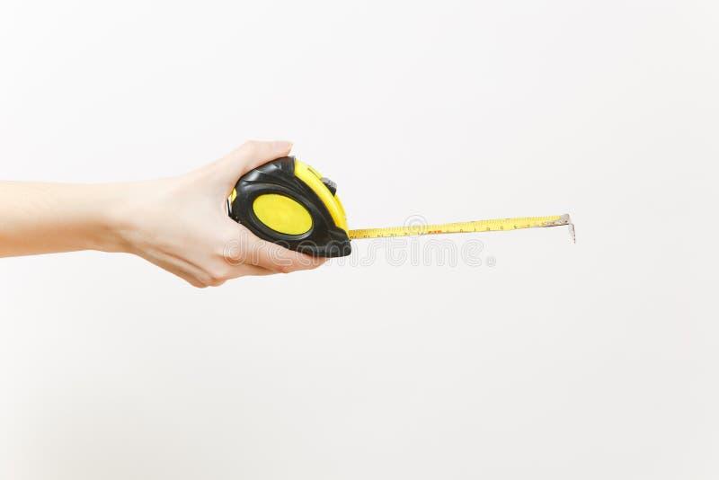 Закройте вверх женской руки горизонтальные владения измеряют ленту изолированную на белой предпосылке Аппаратуры, аксессуары, инс стоковое фото