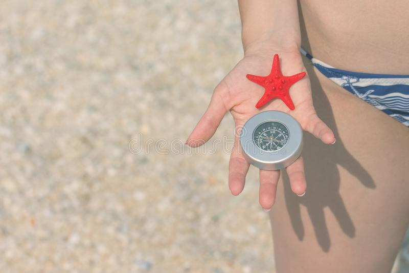 Закройте вверх женской руки держа морские звёзды и компас на beac стоковое изображение