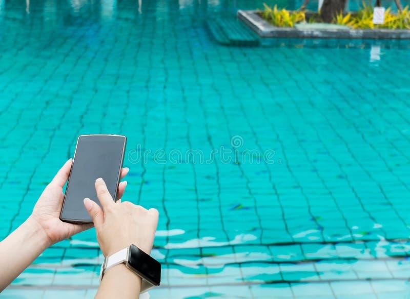Закройте вверх женской руки держа умный мобильный телефон с пустым экраном и нося умный вахту на бассейне роскошной гостиницы стоковая фотография
